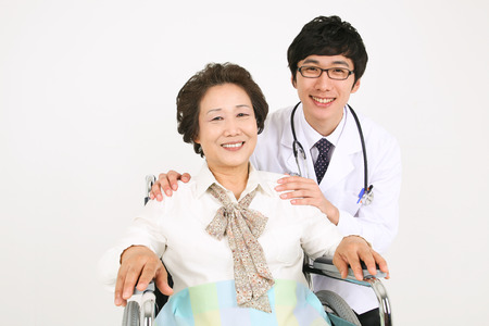 A male doctor eyecontacting with the senior patient sitting in wheelchair Stock Photo