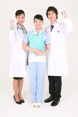 hospital patient: Full shot of A female nurse holding a patient chart as standing between a male doctor and a female doctor