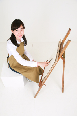 Bird eye shot of a female artist drawing with a pencil sitting in front of the easel