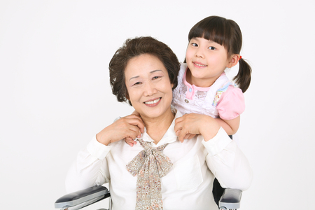 A granddaughter hanging out with her grandmother sitting in a wheelchair Stock Photo