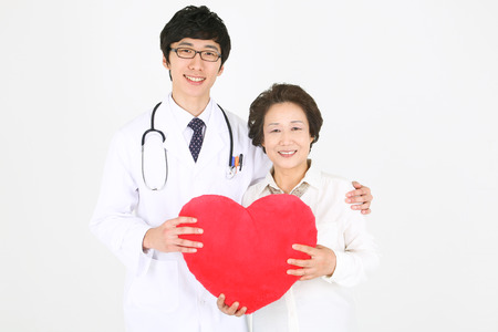 A male doctor and a senior patient holding a big heart shaped cushion together