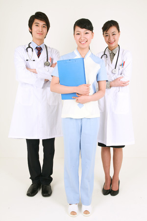 Full shot of A female nurse holding a patient chart as standing between a male doctor and a female doctor