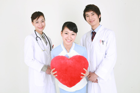 Close up shot of A female nurse holding a heart shaped cushion as standing between a male doctor and a female doctor