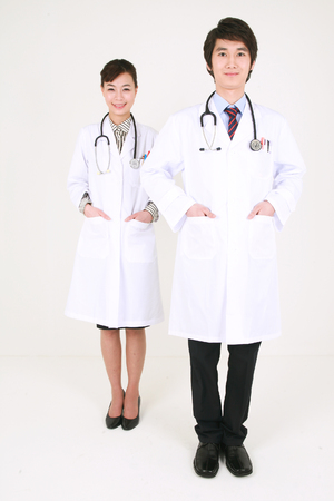 Full shot of A female doctor standing in front of the male doctor as putting hands in the pocket Stock Photo