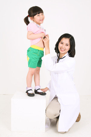 Full body shot of a female doctor applying a stethoscope on a child patient Stock Photo