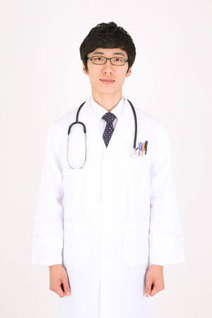 A male doctor standing straight with a stethoscope laid around the neck Stock Photo