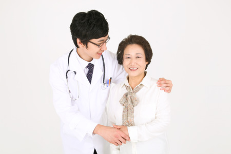 Close up shot of a male doctor putting arms around the senior patient