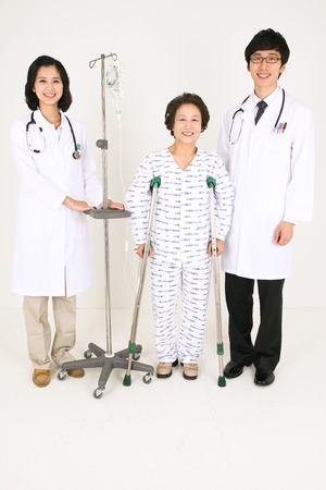 kind hearted: Full body shot of a couple of doctors standing with a senior patient standing on crutches Stock Photo