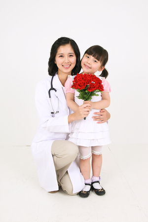 A female doctor holding a young girl patient holding a bouquet of red flowers Stock Photo