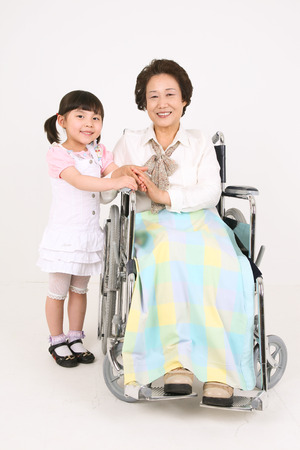 the grand daughter: A senior patient sitting in wheelchair holding hands with the grand-daughter Stock Photo