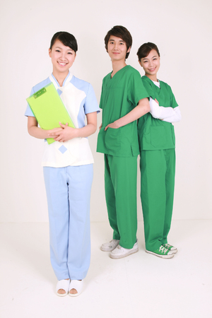 Full shot of A couple of surgeons and a female nurse standing in center holding a patient chart