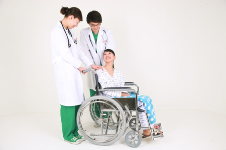 Full shot of A couple of surgeon standing behind the female patient in wheelchair Stock Photo