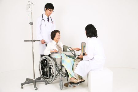 A male doctor and a female doctor diagnosing the senior patient Stock Photo