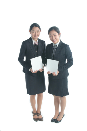 Full shot of Two female hospital coordinators holding sheets of empty papers to the front Stock Photo
