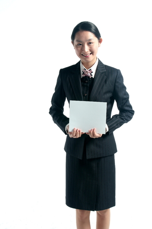 A female hospital coordinator holding a sheet of empty paper to the front in both hands