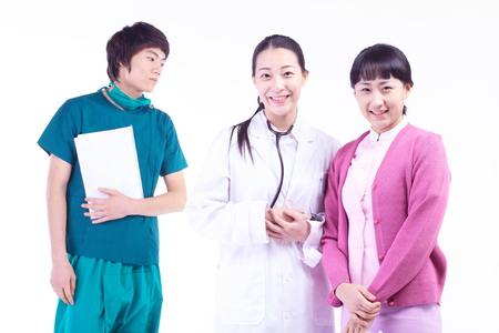 A female doctor, nurse and a male surgeon standing around with a patient chart