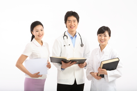 Close up shot of A group of medical personnel holding books and a patient chart Stock Photo