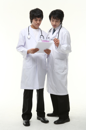 Full shot of Two male doctors looking at a patient chart together as standing Stock Photo
