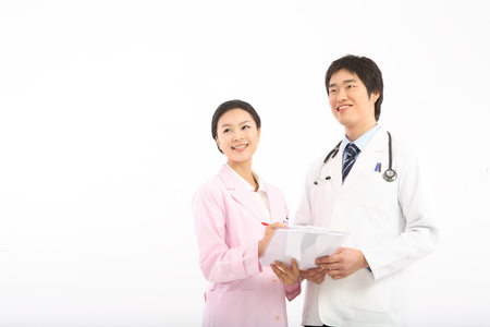 A male doctor and a female doctor holding a patient chart