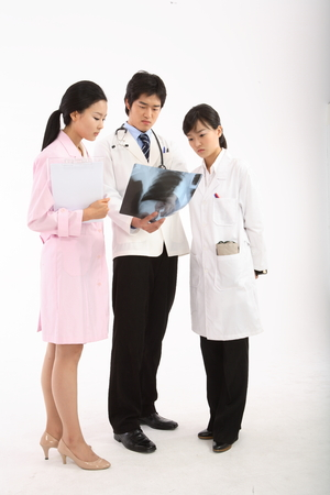 Full shot of A group of medical personnel holding x-ray photographs and a patient chart