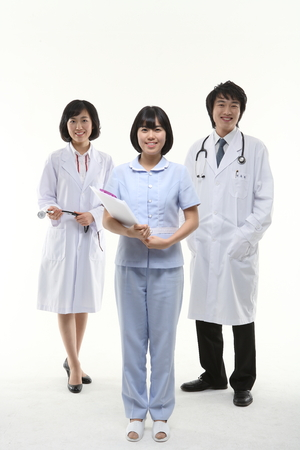 A nurse standing in the center of a group of medical staff Stock Photo