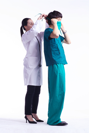 Full shot of A female doctor helping a male surgeon wearing a surgical mask
