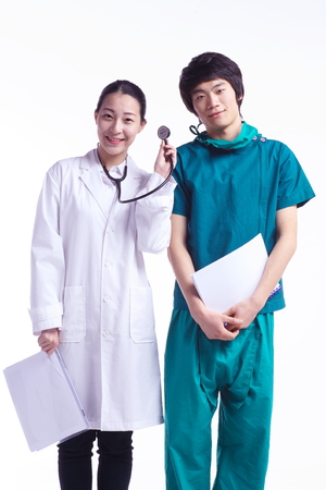 ortopedia: A female surgeon holding a chart and stethoscope as standing next to the male surgeon holding a chart
