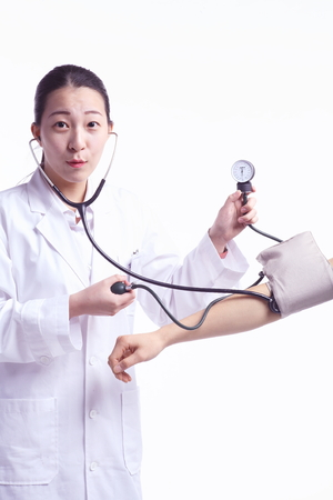 tonometer: Isolated shot of a female doctor using the sphygmomanometer and stethoscope