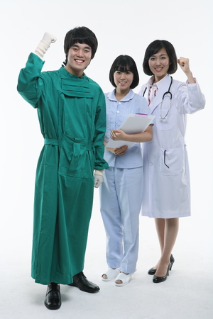 Full shot of A male surgeon, female doctor and nurse showing fists up as in cheering Stock Photo