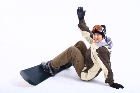 Front shot of A male snowboarder putting ski goggles on forehead waving hand after falling
