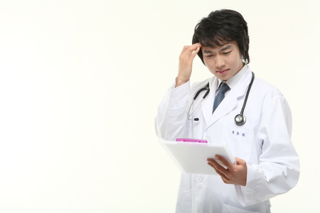 Close up shot of A male doctor scratching his head as holding a patient chart Stock Photo