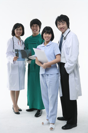 Full shot of A group of medical personnel standing as holding a patient chart and an x-ray photograph with toothy smiles