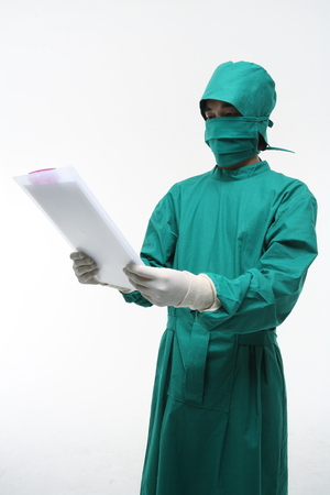 A male surgeon holding a patient chart in surgical gown