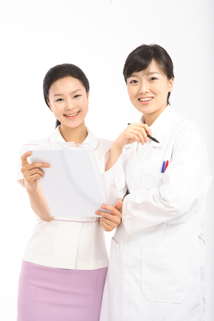A female doctor and nurse holding a patient chart together