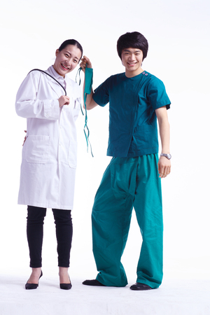 Full shot of A male surgeon holding a surgical mask in hand as standing next to the female doctor holding a stethoscope
