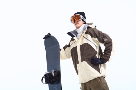 A male snowboarder wearing ski goggles standing next to snowboard as holding it