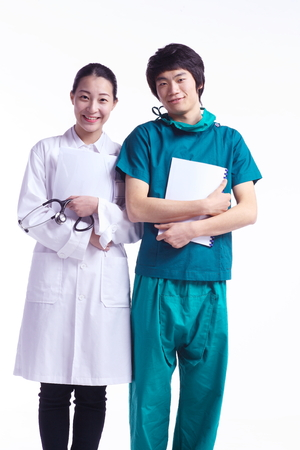 md: A male surgeon and a female doctor holding charts standing next to each other Stock Photo