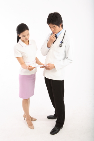 Full shot of A male doctor putting a hand on chin and a female nurse holding a patient chart Stock Photo