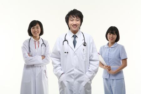 Twee dokters en een verpleegster staan met een toothy glimlach