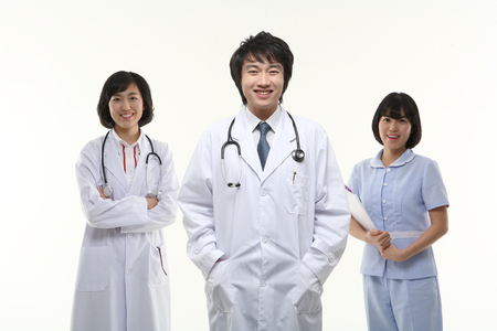 Two doctors and a nurse standing with toothy smile Banco de Imagens