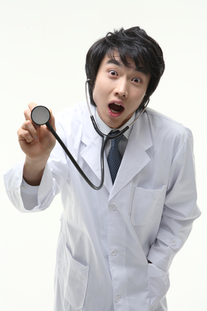 A male doctor pretending to apply stethoscope with a surprised face Stock Photo