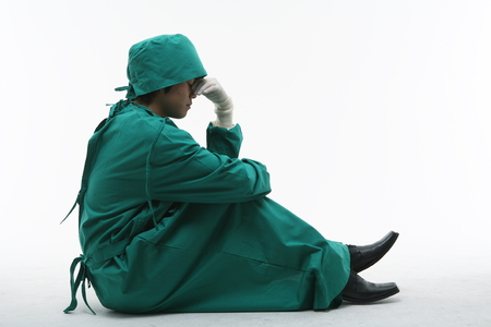 md: Full shot of A male surgeon sitting down covering his face in surgical gown Stock Photo