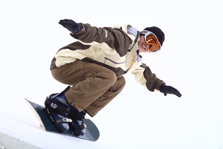 Front shot of A male snowboarder wearing ski goggles snowboarding as squatting down Editorial