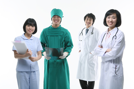 A group of medical personnel standing as holding a patient chart and an x-ray photograph with toothy smiles Stock Photo
