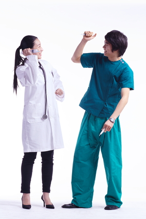 Full shot of A female doctor and a male surgeon pretending to poke each other with injections