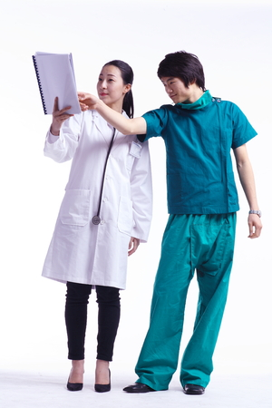 md: Full shot of A male surgeon and a female doctor looking at a patient chart together