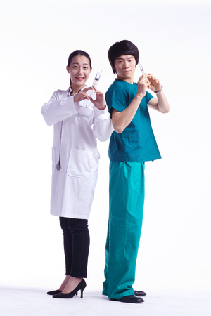 Full shot of A male surgeon and a female doctor holding injections like guns as standing against each others back Stock Photo