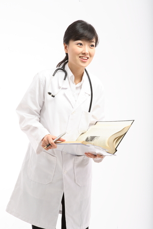 turning the page: A female doctor holding a thick open book as holding a pen