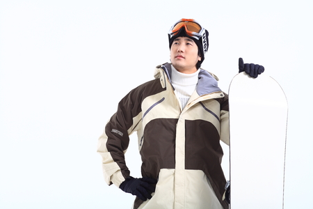Close up shot of A male snowboarder putting ski goggles on forehead standing next to the snowbard as holding it