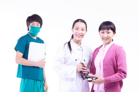 A female doctor, nurse and a male doctor looking at a patient chart together